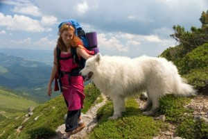 Backpacker girl travelling in the Carpathian mountains with dog